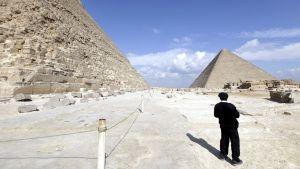 Mustapukuinen, egyptiläinen poliisimies tarkkailee pyramideja.