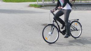 Mies ajaa sähköpolkupyörällä parkkipaikalla