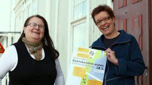 Tuotantosihteeri Heli Karttunen ja tuottaja Hannele Autti esittelevät hymyillen Rantakauden avaus -julistetta Joensuun Pakkahuoneen edessä.