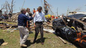 Jay Nixon pitää kättään Obaman oikealla olkapäällä. Takana on tornadon repimä maisema sekä musta henkilöauto, johon on ilmestynyt spraymaalilla maalattuja töherryksiä.