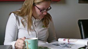 Tanja Perkkiö lukee lehteä.