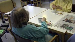 Kaksi vanhusta kahvilla pöydän ääressä