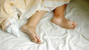 Nainen nukkuu peiton alla.
