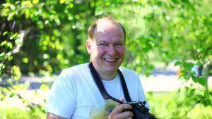 Lintuharrastaja Markku Halonen pitelee käsissään kameraa ja hymyilee