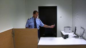 Apulaispoliisipäällikkö Kari Keski-Opas esittelee kuulusteluhuonetta.