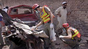 Turvallisuusvirkailijat tutkivat pommin räjähdyspaikkaa Peshawarissa 5.6.2011.