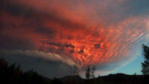 Puyehue tulivuoren uumenista nouseva tuhkapilvi värjäytyy punaiseksi ilta-auringossa Chilessä.