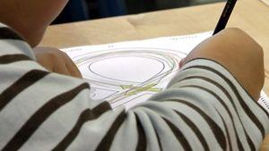 Lapsi piirtää liikenneympyrää.