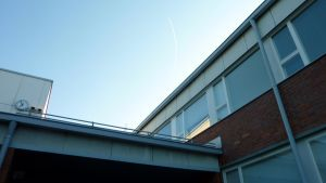 Minna Canthin koulun kello ja katto, taustalla sininen taivas.