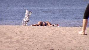 Nainen ottaa aurinkoa Hietaniemen uimarannalla Helsingissä.