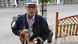 Kuvassa Antero Pohjonen kannattelee World Transplant Games -kisoista saamiaan mitaleita.