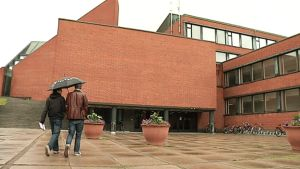 Kaksi opiskelijaa kävelee sisään Aalto-yliopiston teknillisen korkeakoulun pääovesta Otaniemessä.