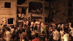 Väkijoukko kerääntyneenä sortuneen talon eteen.