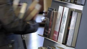 Kirjoja kirjaston hyllyssä ja lainaajan sylissä.