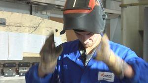 Opiskelija laittaa hitsauskypärää päähän.