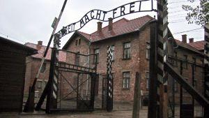 Auschwitzin kuuluisa portti, jonka päällä lukee ARBEIT MACHT FREI.