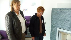 Kuvassa kaksi naista tarkastelee takkaa, johon on asennettu lasinen kipinäsuoja