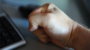 Miehen käsi nyrkissä työpöydällä.