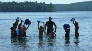 Uimakoululaisia opettajan ympärillä järvessä