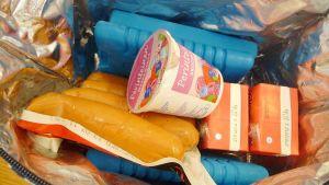 Kuvassa avonainen kylmälaukku jossa makkarapaketti jogurttipurkki ja mehuja.