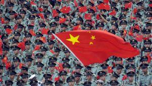 Kiinan Kommunistipuolueen 90-vuotisjuhlallisuuksissa Sotilaat heiluttelevat Kiinan lippuja.