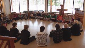 Nuoret istuvat lattialla ympyrässä.