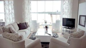 Kuvassa olohuoneessa oleva sohvakalusto, pöytä ja televisio.