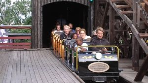 matkustajia linnanmäen vuoristoradassa, kierros on juuri tullut loppuun ja ihmiset iloisia