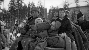 Sotilas hevoskuorman ohjaksissa ja evakuoituja karjalaisia lapsia sekä nainen muuttokuorman päällä istumassa evakkomatkalla.