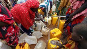 Somalinaiset täyttävät vesikanistereita yhteisen vesilähteen äärellä.