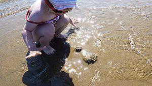 Tyttö leikkii aurinkoisella hiekkarannalla.