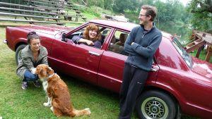 Nainen ja mies auton edustalla koiran kanssa. Toinen nainen nojaa auton ikkunasta.