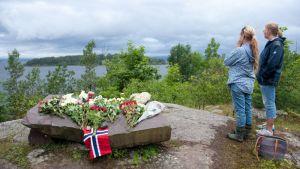 Kaksi tyttöä katsovat Utøyan saarta mantereen puolelta paikasta, johon on tuotu kukkia ja kynttilöitä surmansa saaneiden muistoksi.