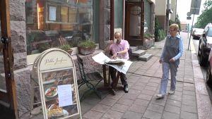 Ulkona kahvittelu miellyttää Mauri Tanskasta. Terveystarkastaja Sinikka Holsti rientää tarkastukselle.