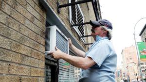 Huoltomies asentaa ilmastointilaitetta talon ulkoseinään.