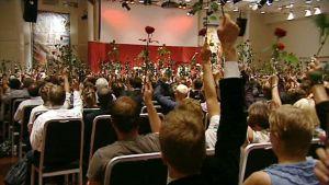 Norjan työväenpuolueen muistojuhlan vieraat kohottavat ilmaan punaisia ruusuja verilöylyn uhrien kunnioituksen merkiksi.