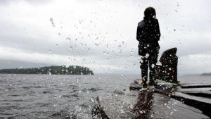 Tyttö kunnioittamassa Utoyan saarella iskussa menehtyneitä muistomerkillä mantereen puolella Utvikassa.