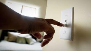 Henkilö sulkee valoja katkaisijasta.