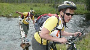 Maastopyöräilijät ylittävät vesiestettä.