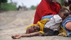 Uupunut somaliäiti makaa lapsensa kanssa tiellä.