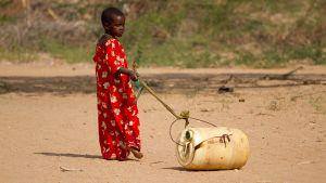 Pieni lapsi vetää perässään täyttämäänsä vesisäiliötä.