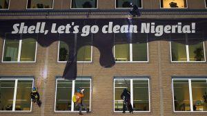 Kansalaisjärjestön jäsenet levittävät Nigerian öljyvuotojen siivoamiseen kehottavan bannerin Shellin pääkonttorin seinälle.
