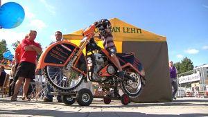 Lapsi maaratamoottoripyörän selässä markkinoilla