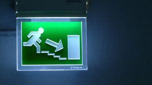 Kuvassa hätäpoistumistielle opastava kyltti hohtaa vihreää valoaan.