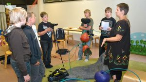 kuudeluokkalaisia poikia opettelemassa videontekoa, ohjaaja oikealla