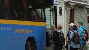 koulubussiin nousevia lapsia ja nuoria