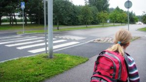 Ekaluokkalainen valmistautuu ylittämään tien suojatietä pitkin matkalla kouluun.