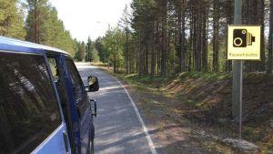 Maantiellä auto  ja tien penkalla Rajavartioston kameravalvonnasta kertova kyltti.