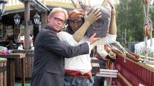 Topi Sukari ja arkkua kantava merirosvohahmo.