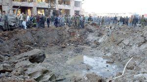 Pelastushenkilöstö tutkii, jossa autopommi räjähti.
